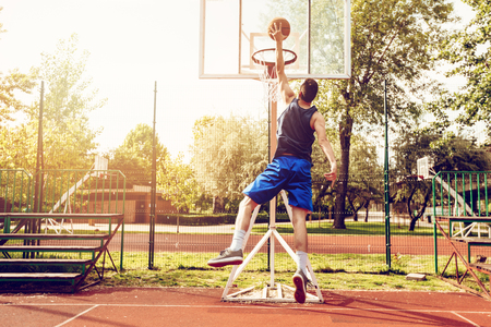 Young street basketball player showing his skills on court. He throw dunk.