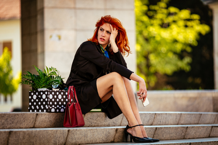 Serious pensive businesswoman sitting on stairs next to a box full of her personal belongings from the office just after she got fired. Stock Photo