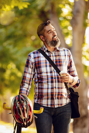 he: Casual businessman going to work by bicycle. He is walking with coffee to go next to bike and thinking.