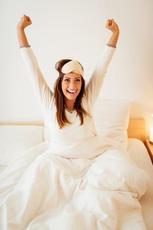 Young beautiful woman with sleeping mask sitting in the bed in morning and stretching. Stock Photo