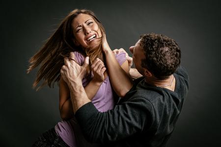 怒っている積極的な夫が彼の妻をヒットしようとしています。 写真素材
