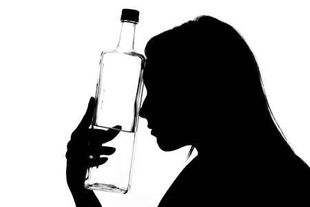 Silhouette of a young drunk woman with a glass bottle.