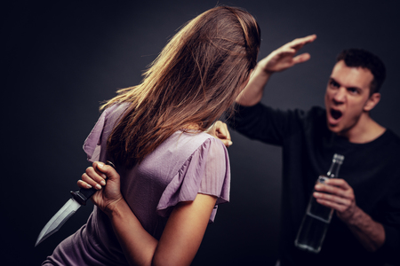 Angry aggressive drunk husband is physically abusing his wife. Selective focus. Stock Photo