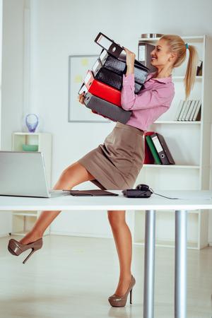 registro: Joven sonriente mujer de negocios que llevaba una pila de carpetas en las manos y mantenerlos para no caer.