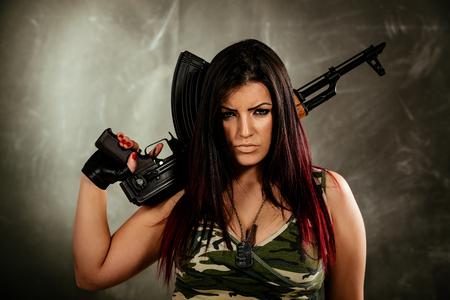 자동 소총을 들고 카메라를 찾고 젊은 매력적인 군사 여자. 스톡 콘텐츠 - 84048690