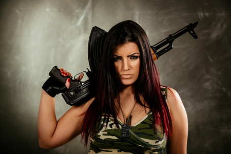 Young attractive military woman holding automatic rifle and looking at camera.