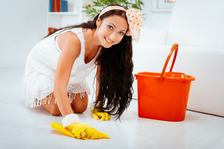 Young beautiful maid scrubbing floor.