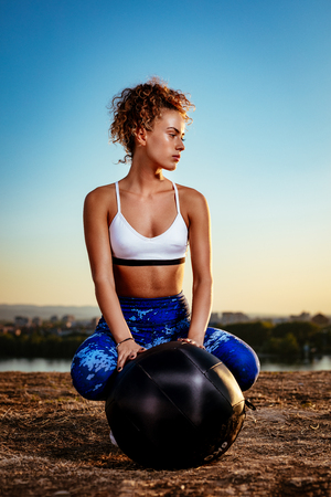 amanecer: Young fitness woman resting afther hard training on the city rooftop. Foto de archivo