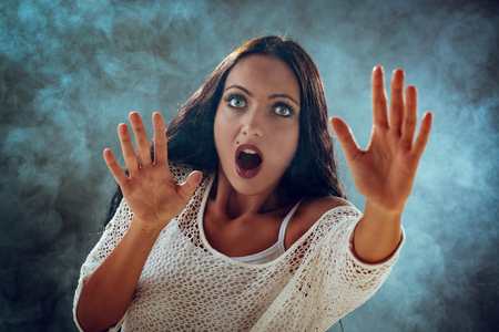 terrified woman: Young stressed woman scared looking through smoke and seeking safety.