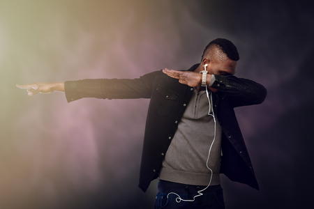 African guy wearing headphones and dancing Dab. Stok Fotoğraf