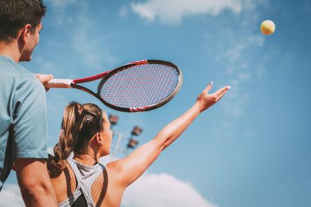 Hermosa jugadora de tenis con instructor practicando servir en la cancha de tenis al aire libre. Foto de archivo