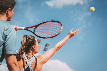 Beautiful female tennis player with instructor practicing serve on outdoor tennis court. Archivio Fotografico