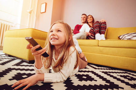 Beautiful young family enjoying a leisure activity at home. They are watching a tv. Selective focus. Stock Photo