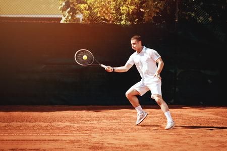 Beautiful young man playing tennis match. Stock Photo