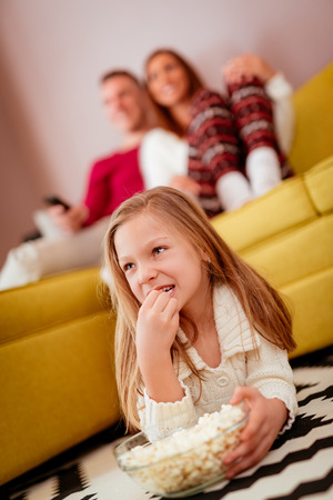 Beautiful young family enjoying a leisure activity at home. They are watching a movie at living room. Selective focus. Stock Photo