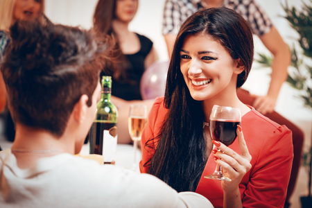 Young cute smiling girl holding a glass of wine on home party. She is looking at his boyfriend. Selective focus. Reklamní fotografie