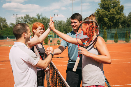 Four young friends giving a high-five after tennis training. Selective focus. Foto de archivo