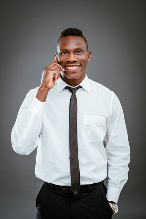 african business: Smiling African businessman using smart phone and looking at camera.