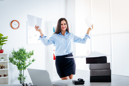 Young stressed businesswoman standing in the office and holding papers. Imagens