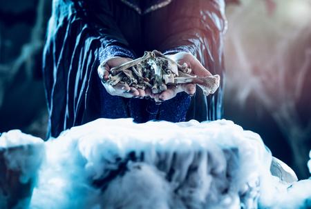 Close-up van de handen die van een heks beenderen boven kokend water voor een het koken gifsoep houden.
