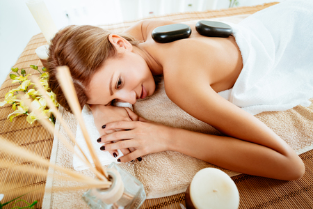 lastone therapy: Young beautiful woman relaxing at spa centre. She is enjoying at stone massage.