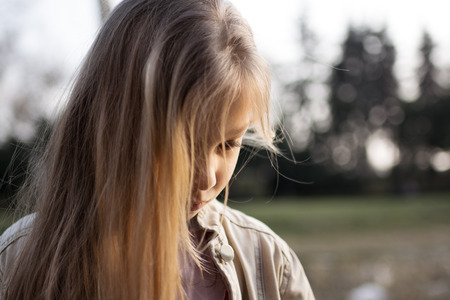 Close-up of a little girl with long hair, standing alone, head bowed, looking down with a sad expression on her face.