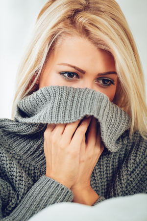 Close-up of a young pensive blonde woman with raised collar of her sweater, over half of the face.