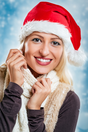 Young pretty blonde girl with santa hat on her head, smiling looking at camera and tucking it into her scarf. Stock Photo