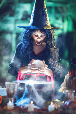 Portrait of young angry witch with awfully face in creepy surrounding watching the future in magic ball above boiling potion.