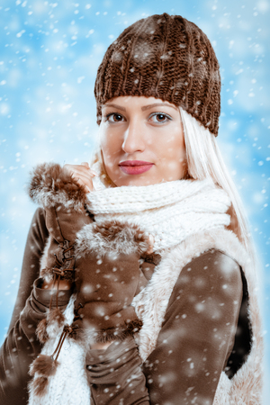 Beautiful young girl in winter clothes with a wool cap and fur gloves, sticks to the wool scarf in which is tucking while snow falling.