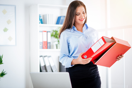 Young successful businesswoman standing in the office and holding binder. Imagens