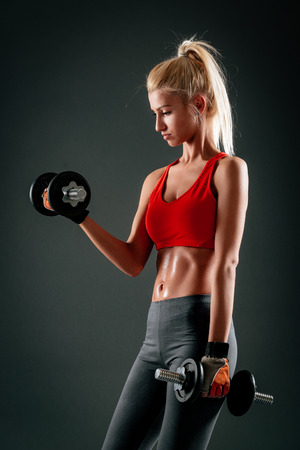 Studio portrait of athletic girl lifting dumbbell, in dark background. Looking at dumbbell. Stock Photo