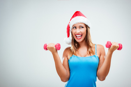 Happy fitness woman with a Santa's cap on her head, lifting dumbbells and smiling cheerful, fresh and energetic. White background. Archivio Fotografico