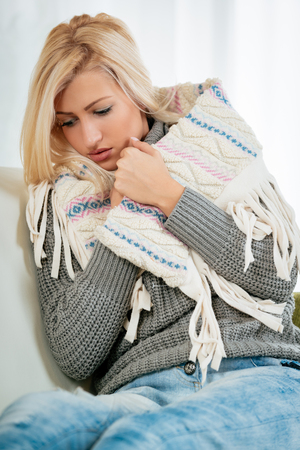 Beautiful blonde girl is sitting on the couch, dressed in a warm wool sweater, tucking a shawl with a sad expression on her face.