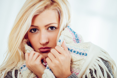 Close-up of beautiful young blonde girl tucked in a woolen scarf. With serious expression on her face looking at camera.