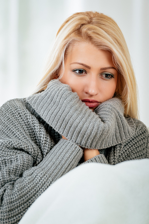 Portrait of a young pensive blonde woman with raised collar of her sweater, over half of the chin. Stock Photo