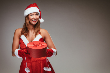 Beautiful young smiling woman in Santa Claus costume holding red present and looking at camera. Archivio Fotografico