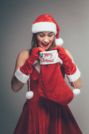 Cheerful beautiful young woman in Santa Claus costume enjoying and surprisingly looking what is inside of a red christmas stocking. Archivio Fotografico