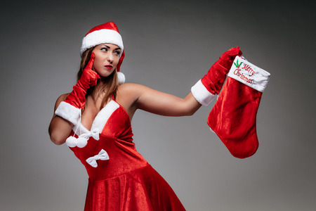 Beautiful young smiling woman in Santa Claus costume thinking and holding red christmas stocking.
