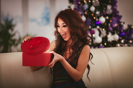 Cheerful beautiful young woman enjoying Christmas at home, opening gift and surprisingly looking what is inside.