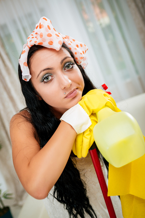 Young beautiful tired housewife holding a cleaning equipment. Looking at camera.