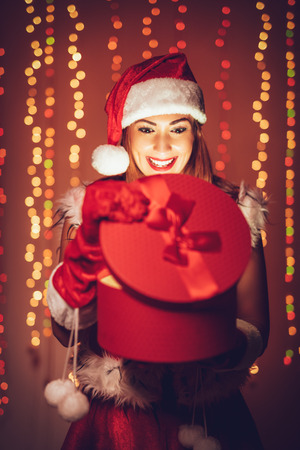 Cheerful beautiful young woman in Santa Claus costume enjoying at opening gift and surprisingly looking what is inside. Фото со стока