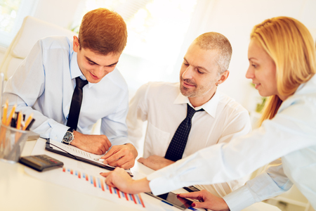 Business people having a meeting. Three business people looking at document and discussing in the office. Stock Photo