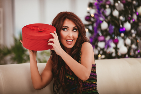 Pretty young smiling woman enjoying Christmas at home. She is holding gift with surprisingly face.