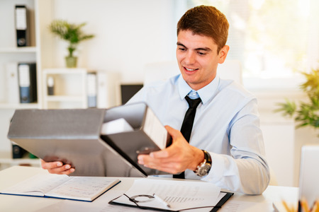 Young handsome smiling businessman working in the office. Stock Photo
