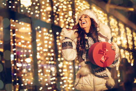 Cheerful young woman with red present having fun in the city street at Christmas time.