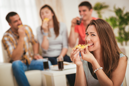 Four cheerful friends hanging out in an apartment. Smiling girl sitting foreground and eating pizza. Selective focus.  Foto de archivo