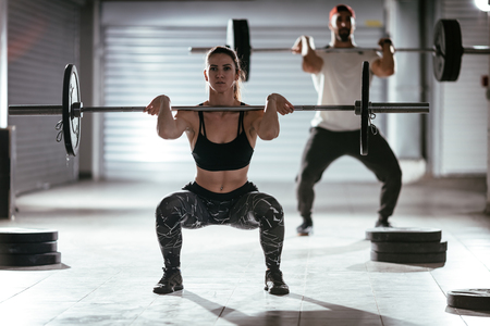 Young muscular couple doing a high pull exercise with barbell on cross training at the garage gym. Foto de archivo