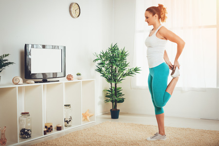 Beautiful muscular girl doing stretching exercise with online personal trainer on a tv at the flat.