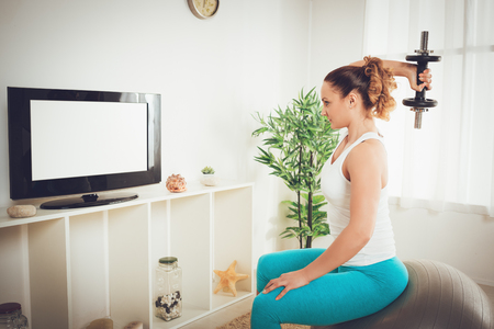 Beautiful muscular girl doing exercise with dumbbell to strengthen tricep with online personal trainer on a tv at flat.
